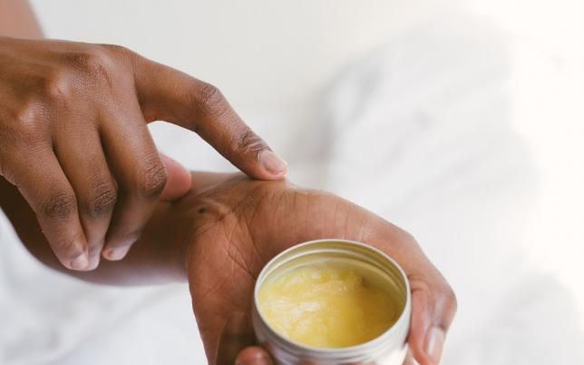 Femme appliquant une huile sur sa main